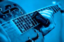 blue tinted photo of acoustic guitar being played with a slide