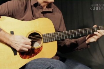 Close up photograph of man playing an acoustic guitar, demonstrating a harmonized major from the lesson video