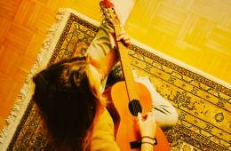photo of guitar student seated on a rug taken from above
