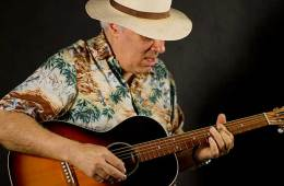 Fred Sokolow playing a blues riff on an acoustic guitar