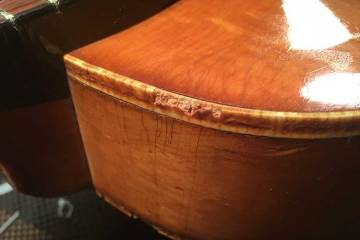 closeup of an acoustic guitar's binding that has deteriorated due to the aging and chemical breakdown process known as celluloid rot