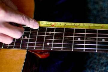 closeup of an acoustic guitar fretboard and a tape measure being used to measure scale length