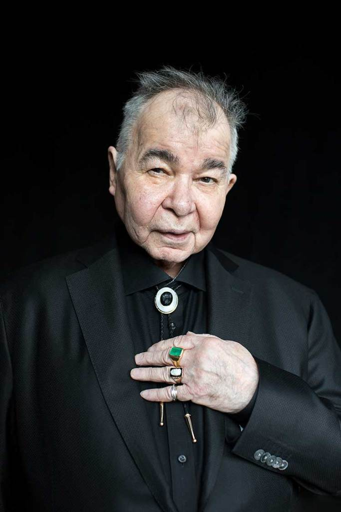 John Prine in his older years in a black suit with bolo tie