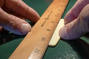 placing the bottom edge against a the saddle of a guitar placed against a ruler