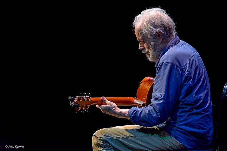 seated Leo Kottke performing solo acoustic guitar onstage