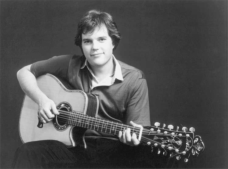 Leo Kottke seated holding a 12-string acoustic guitar in 1970