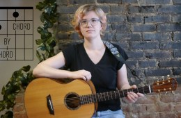Kate Koenig holds her guitar against a brick wall