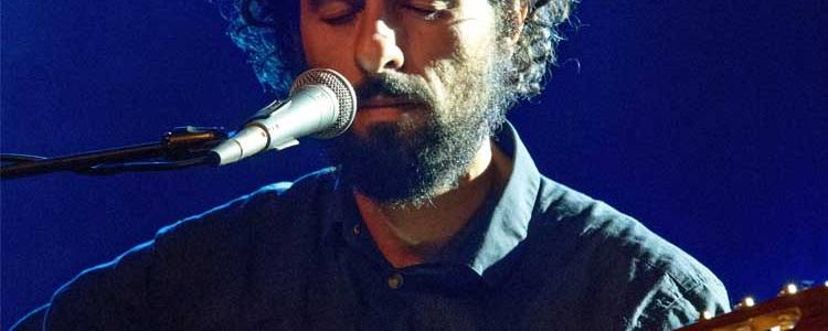 singer-songwriter José González sings into a microphone while holding an acoustic guitar