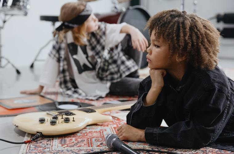 two friends pose in a music studio with their guitars