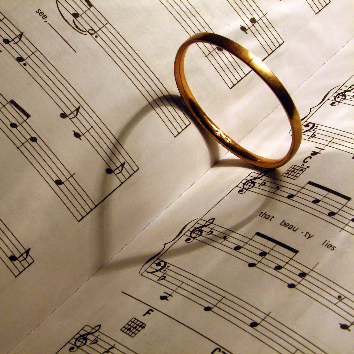 Wedding ring making heart shaped shadow on sheet music.