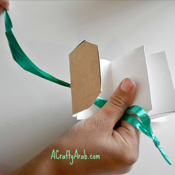 Tie the ends together. Thread the folded end of the ribbon trough the hole from the inside out. The knot will catch on the inside of the hook.