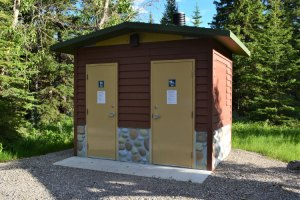 Fancy pit toilet building with faux-stone siding at base
