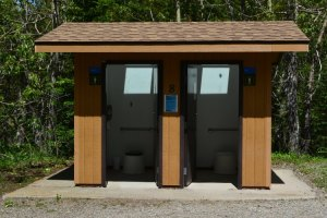 Dual pit toilet made of wood and concrete