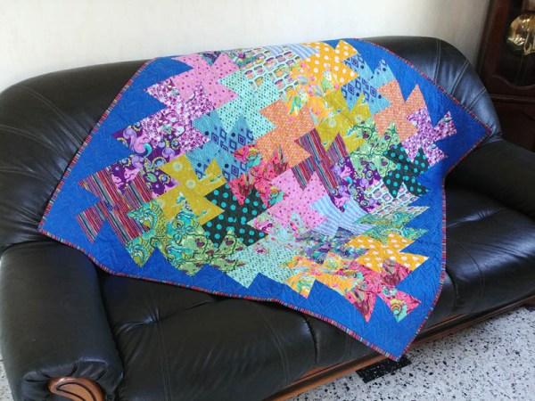 Acropatch-Panneau mural-Twisting_pinwheels-Motif-Quilting-Splash-fil-multicolore-sur un canapé 3 places