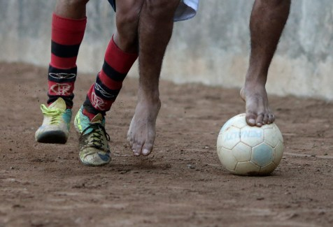 """Players battle for the ball during a Sunday """"pelada"""" soccer match in the Borel favela of Rio de Janeiro, a World Cup host city, May 4, 2014. Sunday soccer is a decades-old tradition when Brazilians of all walks of life play on the beaches, in the slums, and on the streets matches that are known as """"peladas"""" or """"naked"""". Pelada can refer to a street match where everyone plays barefoot with ÒnakedÓ feet, or a match on a grassless ÒnakedÓ field, or a match with a ball so worn that it is Ònaked.Ó With the 2014 World Cup just one month away, people of all walks of life in the host cities are spending their Sundays practicing the sport for which their country is about to become the global stage. The tournament will take place in Brasilia, Belo Horizonte, Rio de Janeiro, Sao Paulo, Natal, Fortaleza, Salvador, Porto Alegre, Curitiba, Cuiaba, Manaus, and Recife. Picture taken May 4, 2014. REUTERS/Ricardo Moraes (BRAZIL)"""