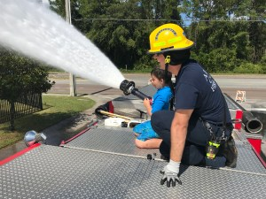Fire Rescue personnel allowing a kid to spray water at a community event
