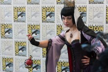 """'Snow White's' Evil Queen dangles an """"apple"""" for photographers."""