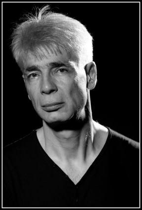 Un homme d'une cinquantaine d'années, aux cheveux blancs, Pierre-François Kettler, pose devant la photographe (moyen format N&B).