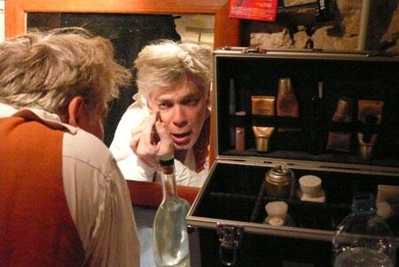 Un homme d'une quarantaine d'année se maquille devant un miroir