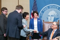 Marilyn Cohen shaking hands with Gov. Jay Inslee. Pictured left to right: Curt Kohlwes, Executive Legislative Assistant, Sen. Marko Liias 21st District-Lynnwood, Marilyn Cohen, NW Center for Media Literacy, College of Education, UW, Carolyn Logue, Washington State Library Association and Gov. Jay Inslee.