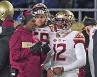 Deondre Francois and Head Coach Willie Taggert go into a strategic planning session on the sideline again Notre Dame November 10, 2018