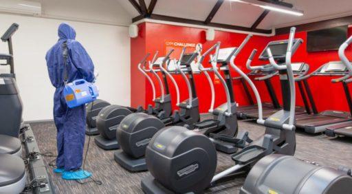 Person wearing blue hazmat suit sterilising machines at an indoor gym