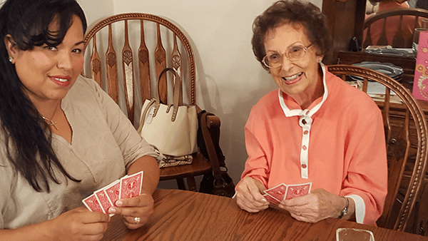 Caregiver and senior playing cards