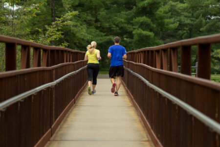 a couple jogs along a trail at deer lakes park in pittsburgh pennsylvania