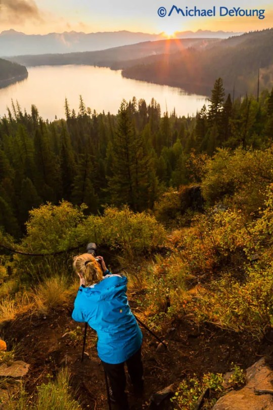 Photographer at sunset, overlooking Holland Lake and the Mission Mountains, Montana