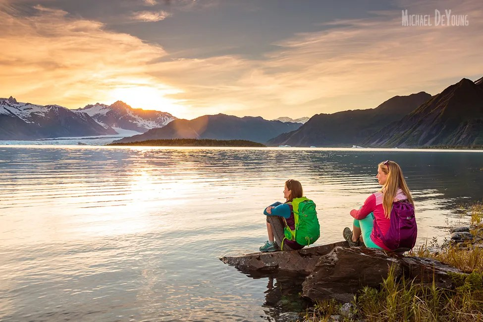 Alaska Adventure - Young women watching sunset over Bear Glacier in Kenai Fjords National Park by Michael DeYoung