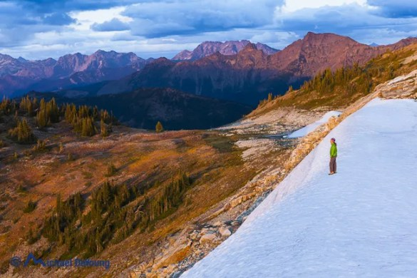 Image of woman standing on a lingering snowfield at sunset on Devil's Dome, Pasayten Wilderness, North Cascades, Washington