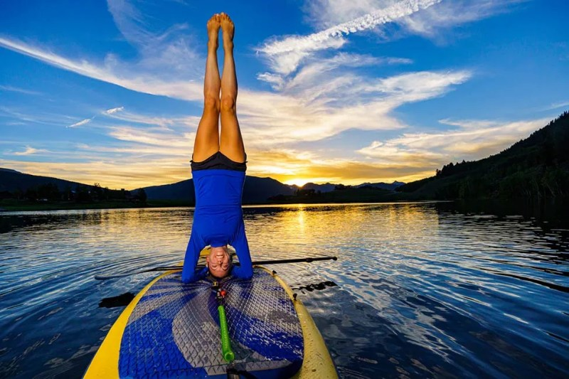 Woman doing a head stand on a stand up paddle board. Photo © Michael DeYoung
