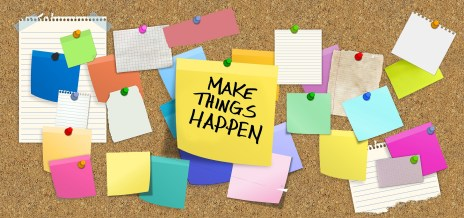 "a bulletin board with many post-its, one of which says ""make it happen"""