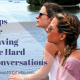 two white women sit and have a conversation while they look out over the water