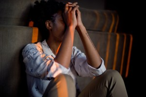 a young Black woman sits against a wall, her hands balanced on her knees and covering her face