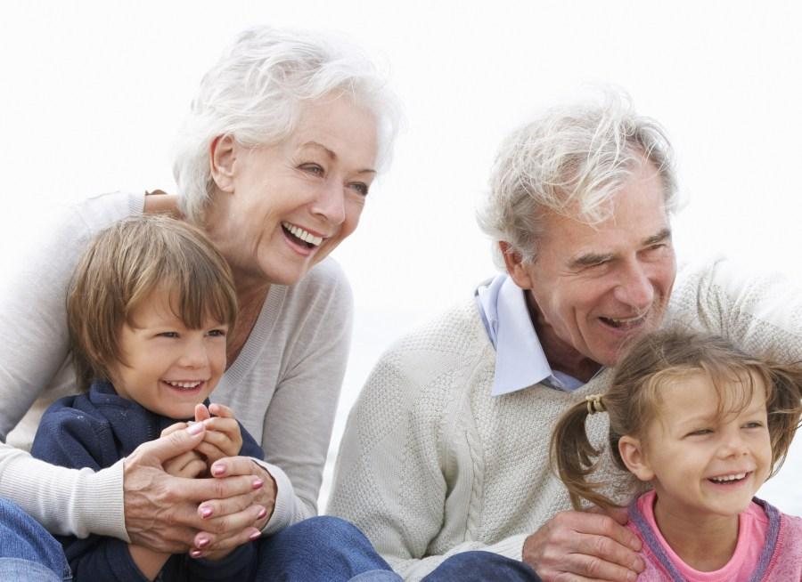 Grandparents And Grandchildren Sitting On Beach Together