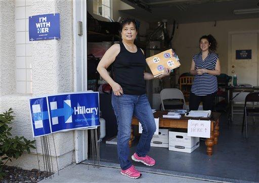 En esta fotografía del 12 de febrero de 2016, la estadounidense de origen chino Cynthia Ameli, al centro, recibe materiales de Sarah Gibson antes emprender labores de apoyo a favor de la precandidata demócrata Hillary Clinton en Las Vegas. Los electores estadounidenses de origen asiático son el grupo de crecimiento más grande en Estados Unidos y tanto el partido Republicano como el Demócrata los cortejan en busca de su voto. (AP Foto/John Locher)