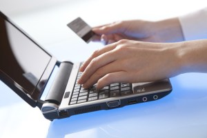 Woman's hand holds a credit card while entering data in laptop