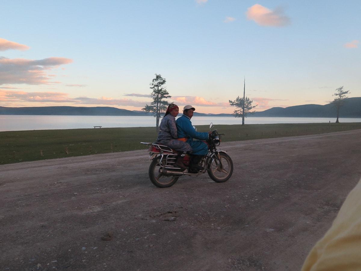Chuwsgulsee mit mongolisches Paar auf einem Motorrad im Vordergrund