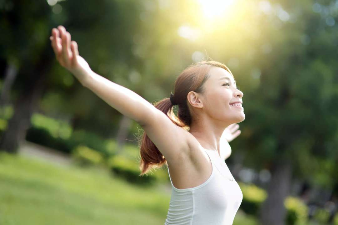 carefree, cheering young Asian woman