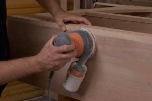 Using an orbital sander to prepare a custom cabinet for the finishing process