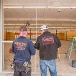 A Cutting Edge Glass & Mirror Employees Working On Family Dollar Storefront