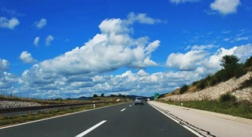 青空のハイウェイを走る車