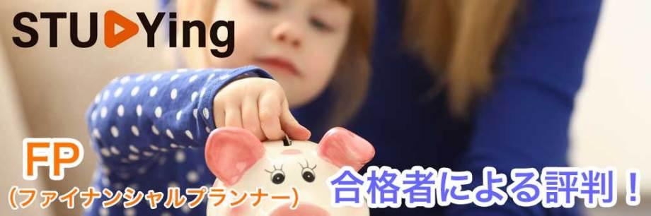 ピンクの豚の貯金箱に硬貨を入れる小さい女の子