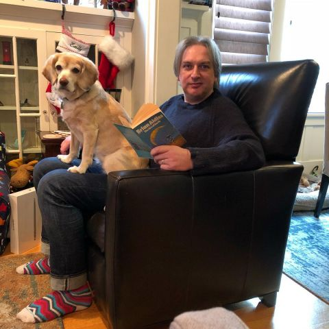Jeremy Keith reading in a chair with a dog