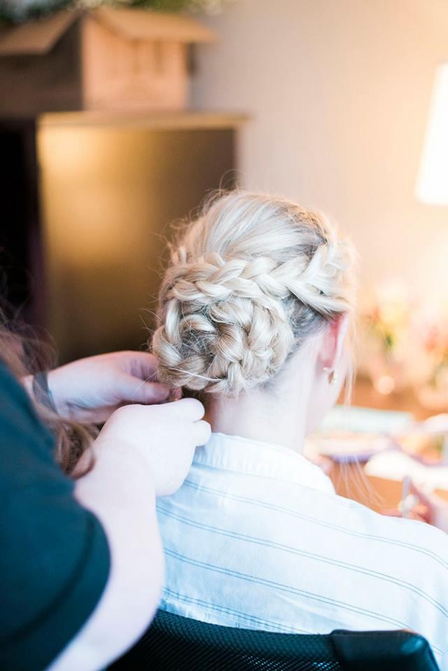 A woman braiding a bride's hair into an updo