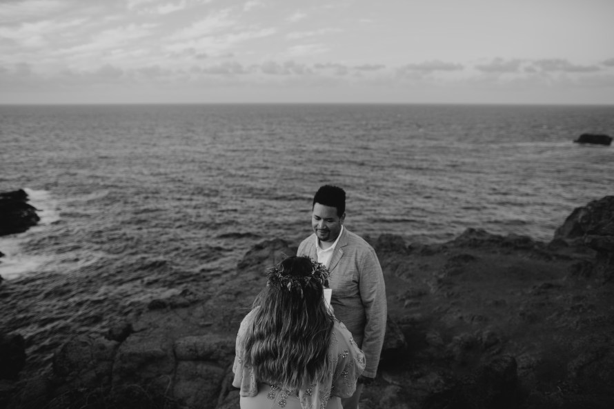 Husband looking at wife while she reads her renewal vows on the cliffs in Kahakuloa Maui