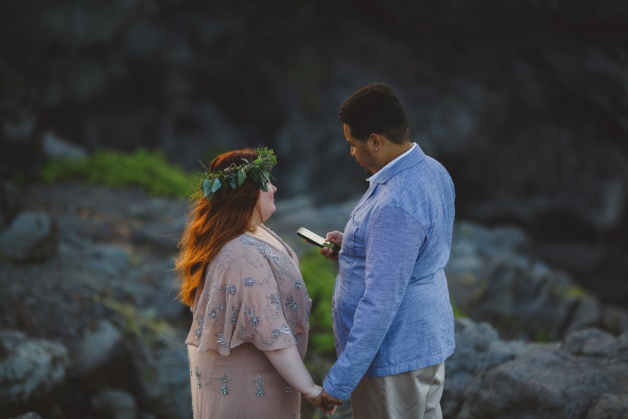Husband reading renewal vows to his wife on the cliffs in Kahakuloa Maui