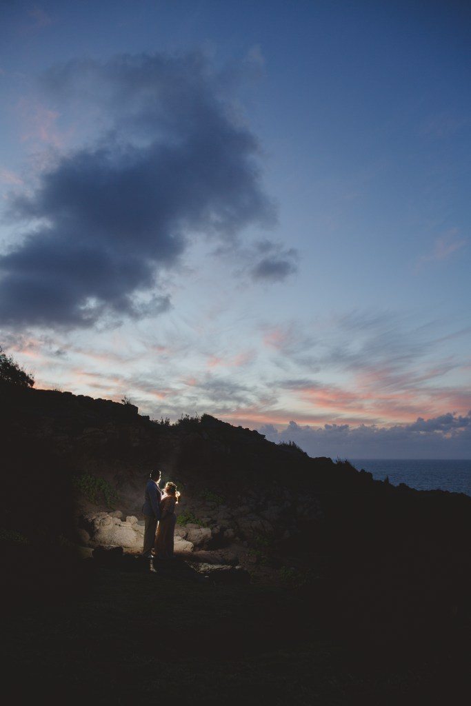 Interracial couple embracing on the cliffs in Kahakuloa Maui as the sun sets behind them