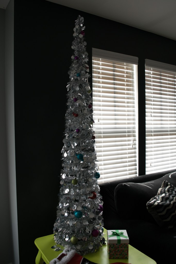 Silver tinsel tree with brightly colored ornaments